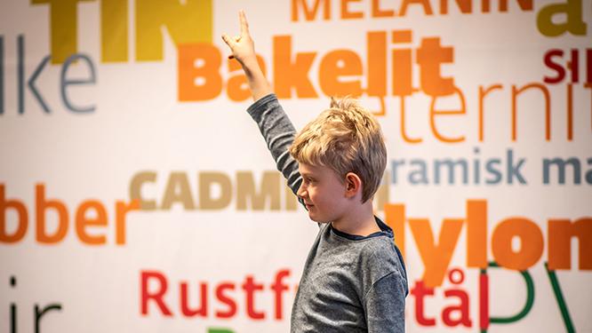 Skoledreng rækker fingeren i vejret.